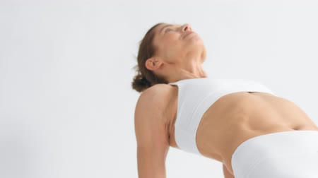 Senior woman in white space practice yoga panned camera movement