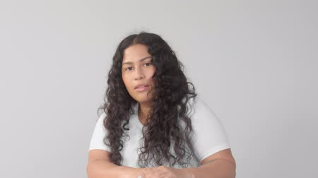 manken : Mixedr ace young plus size woman without makeup in studio on grey background poses to the camera. New beauty, new identity without gender Stok Video