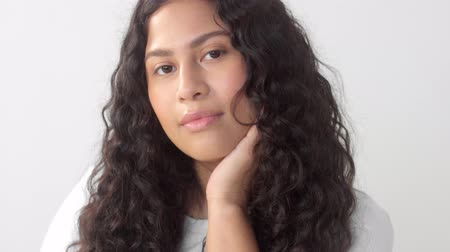 definição : Mixed race plus size woman without makeup in studio watching to the camera and touch her face Stock Footage