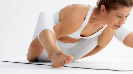 Senior woman in a white space in white yoga outfit practice yoga and made a turtle position. Closeup of foot lifted up