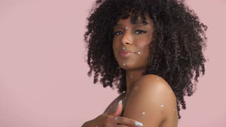 Mixed race black woman with curly hair covered by crystal makeup on pink background in studio Close up smiling and touching her hair dancing