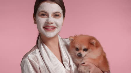 pomačkání : 30s brunette woman with clay facial mask on holding a small fluffy dog in hands. home self-care treatment