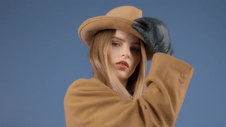 Fashion editorial portrait of blonde model touches a hat on wears an outdoor outfit