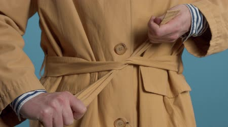 Closeup of mans hand tighten the belt of jacket. Colorful stylish look