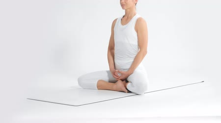 Senior woman in white space practice yoga sits in lotus position tilt camera move Wideo