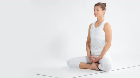 elliler : Senior woman in white space practice yoga sits in lotus position pan movement dolly