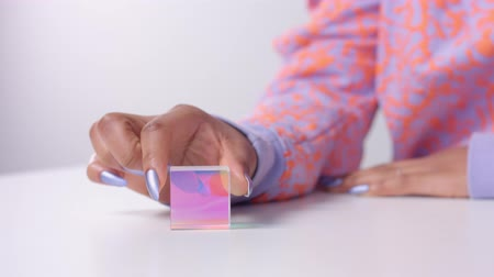 closeup of female hand with violet metallic manicure rolling a rainbow crystal cube and put it on her hand Wideo