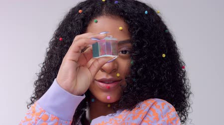 norms : Mixed race black woman with creative avangard makeup simple colorful dot makeup on flawless skin watching to the camera through a crystal colorful rainbow cube
