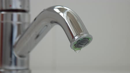 palmo : Closeup of a flowing faucet with water drops falling. Moderate consumption concept