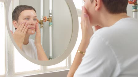 masaj : Young woman in bathroom full of daylight approach to the mirror and put some face cream on. Self-care home treatment for healthy skin