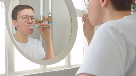 sıkıcı iş : Young caucasian woman with short haircut and glasses in bathroom clean her teeth watching to the mirror Stok Video