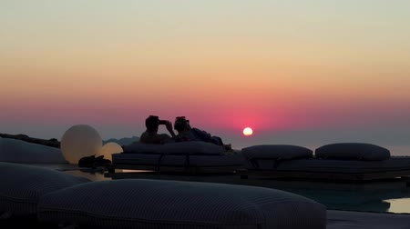 УВР : Couple watches Sunset, Santorini Greece