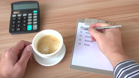 satysfakcja : customer filling up a customer Survey while having a cup of coffee