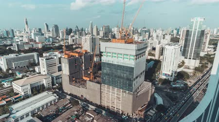 Bangkok, Thailand - Sep 18, 2018: 4k UHD day to night holy grail time-lapse of building construction site in Bangkok city, end with traffic light trails and rain, aerial cityscape view Stock Footage