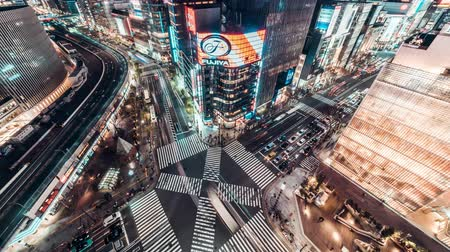 ginza : 4K UHD Aerial view time-lapse of Ginza road intersection at night, crowded people walking on zebra crossing and car traffic light trails. Asia transportation, Asian city life, or Japan tourism concept Stock Footage