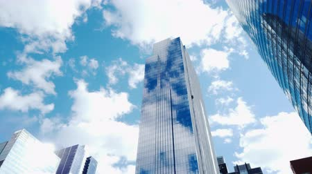 экономический : 4K UHD Motion time-lapse of buildings in business district, sunny day fast moving cloud. Financial economy, construction industry, advanced internet technology, or modern company organization concept