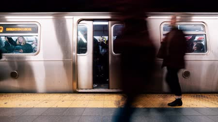 4K UHD Time-lapse of unidentified people waiting and boarding train at Times Square subway station platform in New York city, USA. American city life, or public transportation concept. Zoom out effect