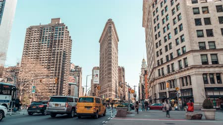 4K UHD time-lapse of car traffic and people walking at Flatiron building district, New York City, USA. American city life, America tourist attraction, travel landmark, or transportation concept