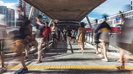 Fast motion time-lapse of crowded Asian people walking on elevated public pedestrian walkway. Commuter lifestyle, Asia city life, or transportation concept. Zoom out then still Stock Footage