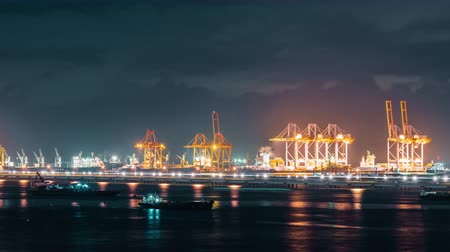 Time-lapse of cranes loading shipment containers in cargo shipping port at night. Import or export business, logistic industry, or freight transportation concept. Zoom out effect