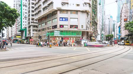 Wan Chai, Hong Kong - July 4, 2019: 4K motion panning time-lapse of crowded people and car traffic transport across road intersection in Hong Kong. Commuter transportation, or Asian city life concept