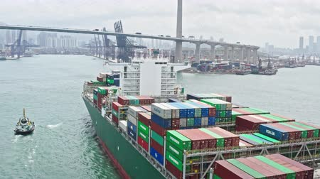 docking : Large cargo ship transporting shipment container from China arriving Hong Kong port, bridge and city background, drone aerial view. Freight transportation, import export business or industrial concept