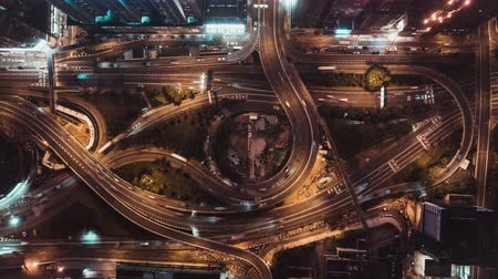 4K UHD top view time-lapse of car traffic at night on multiple lane highway, winding road, and roundabout in Hong Kong city. Commuter, city life, or land transportation concept