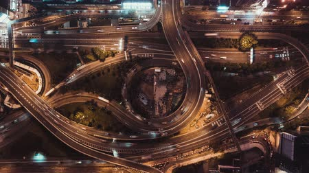 4K UHD top view time-lapse of car traffic at night on multiple lane highway, winding road, and roundabout in Hong Kong city. Commuter, city life, or land transportation concept. Zoom out camera Stock Footage