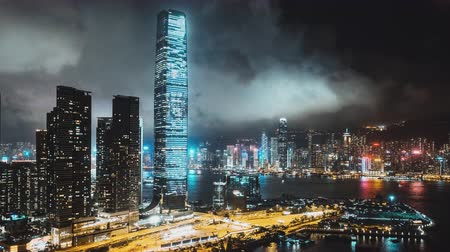 icc : 4K UHD hyperlapse time-lapse of Hong Kong cityscape at night at Victoria Harbour, drone aerial view. Asia travel destination, Asian tourism, modern city life, or business finance and economy concept