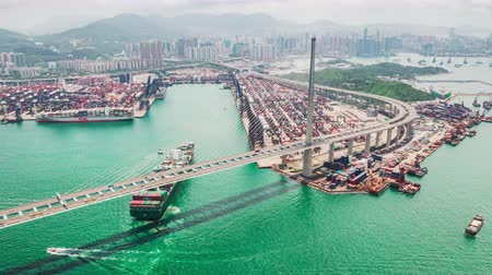 4K UHD hyperlapse timelapse of Stonecutters bridge and Hong Kong port with cargo container ship, crane, and car traffic. Logistic industry or freight transportation business concept, drone aerial view