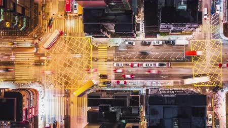 4K UHD Time-lapse of car traffic on road and people crossing street at night in Hong Kong downtown district, drone aerial top view. Commuter, Asia city life, or public transportation concept, Panning