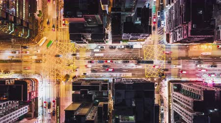 4K UHD Time-lapse of car traffic on road and people crossing street at night in Hong Kong downtown district, drone aerial top view. Commuter, Asia city life, or public transportation concept