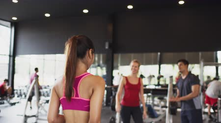Asian woman greet Caucasian friend exercising with male personal trainer in fitness gym or sport club. Recreational activity, multiethnic friend group, or healthy lifestyle concept. 4K UHD slow motion Stock Footage