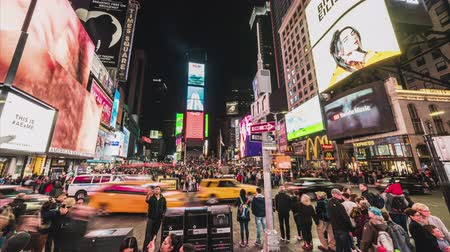 New York City, United States - Mar 31, 2019: Crowded people, car traffic transportation and billboards displaying advertisement at night in Times Square. American lifestyle or modern city life concept