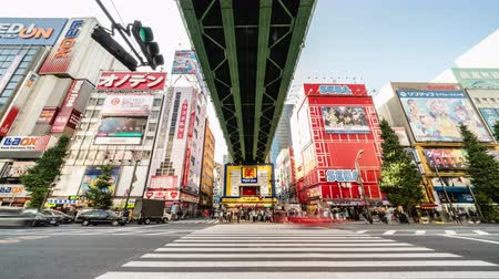 Tokyo, Japan - Nov 2, 2019: time-lapse of crowded people walking crossing road, car traffic transport at Akihabara. Tourist attraction, Japan tourism, Asia transportation or Asian city life. Tilt down
