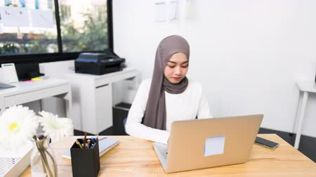 indonesia : 4K Hyperlapse time lapse of beautiful Asian muslim woman working using laptop in modern office. Small business company owner, startup entrepreneur, or working woman lifestyle concept Stock Footage