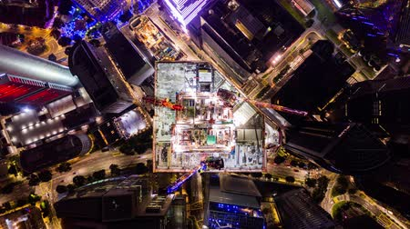 4K time-lapse of under construction site, crane, and car traffic transportation at night in Singapore city downtown. Drone aerial top view. Industrial business or civil engineering technology concept