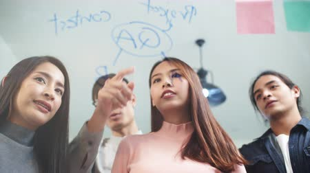 Young Asian woman writing glass wall with sticky notes, leading creative team group meeting in modern office. Business people teamwork, colleague coworker project brainstorm, or idea sharing concept Stock Footage