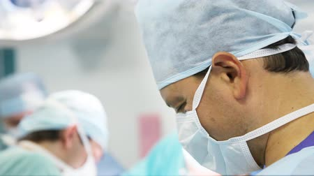 cirurgião : male surgeon with his team working in operation room