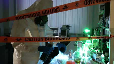 ученый : Scientist behind the caution tape in laboratory with equipment