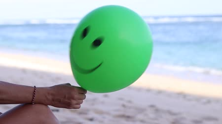 léggömb : Young woman cheerfully sitting on the beach with green balloon. Bali, Indonesia. Full HD, 50fps.