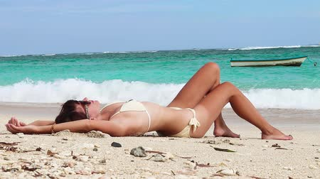 banhos de sol : Woman laying on the beach of Bali island, relaxing and sunbathing, enjoy life. Indonesia.