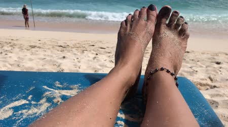 купальный костюм : Woman feet on a beach chair on the paradise tropical beach of Bali island, Indonesia.