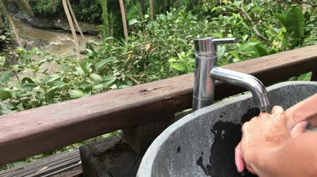 purificado : Woman washing her hands outside with a beautiful tropical view. Freshness and ecology concept. Bali island. Stock Footage