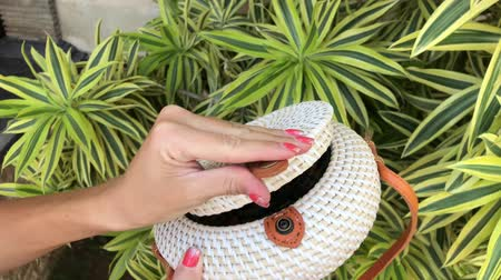 vime : Closeup of woman hands with handmade stylish rattan handbag. Ata bag, eco bag. Rattan bag on a green nature background. Vídeos