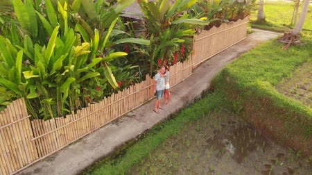 air kiss : 4K aerial drone footage of young couple huging on the rice field close to the luxury villa at sunset time. Bali island.