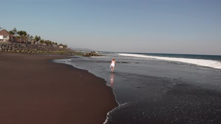 ave : 4K Aerial flying footage of young woman in white dress walking on the black volcanic beach, Bali island.