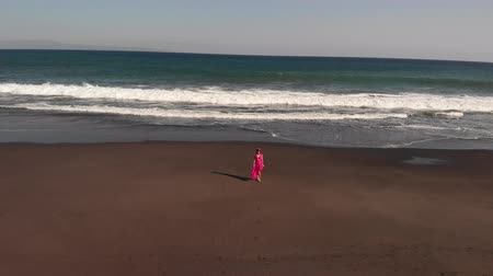 ave : 4K Aerial flying footage of young woman in pink dress walking on the black volcanic beach, Bali island.