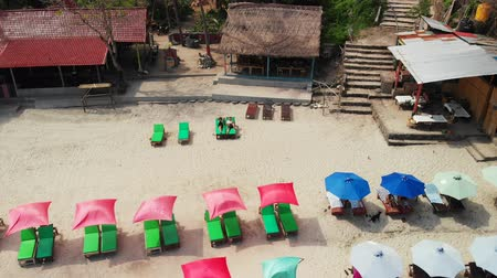 deck chairs : Aerial drone video of young honeymoon couple on the tropical beach of Bali island. Stock Footage