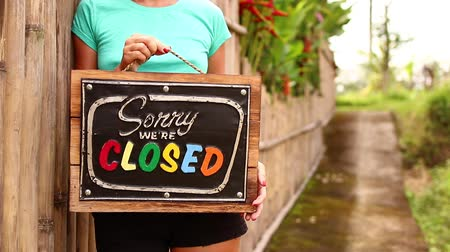sorry : Woman hands with closed sign board on a tropical nature background. Bali island.